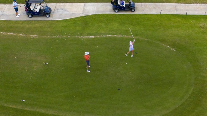A golfer practices her swing before teeing off at the North Palm Beach Country Club in North Palm Beach. The Jack Nicklaus-designed golf course, which has been closed since last month amid the novel coronavirus pandemic, will reopen to members on Wednesday, and to the general public on Thursday.