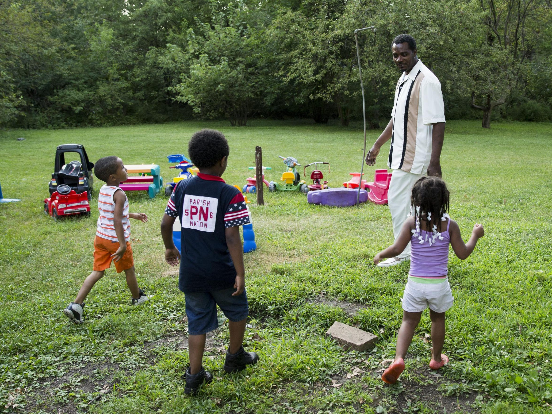 Keith Cooper plays with grandchildren at his home in