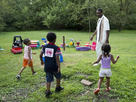 Keith Cooper plays with grandchildren at his home in Country Club Hills, Ill.