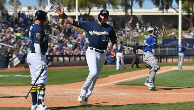 The Brewers' Travis Shaw congratulates left fielder Christian Yelich  as Yelich scores  against the Dodgers during the fourth inning Sunday at Maryvale Baseball Park.