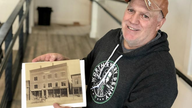 Penny Pinchers Brewing Co. co-founder Jody Barton with an old picture of the storefront where he is opening the brewery. The building has been around for hundreds of years - at one time home to a consignment shop, bakery and pharmacy.