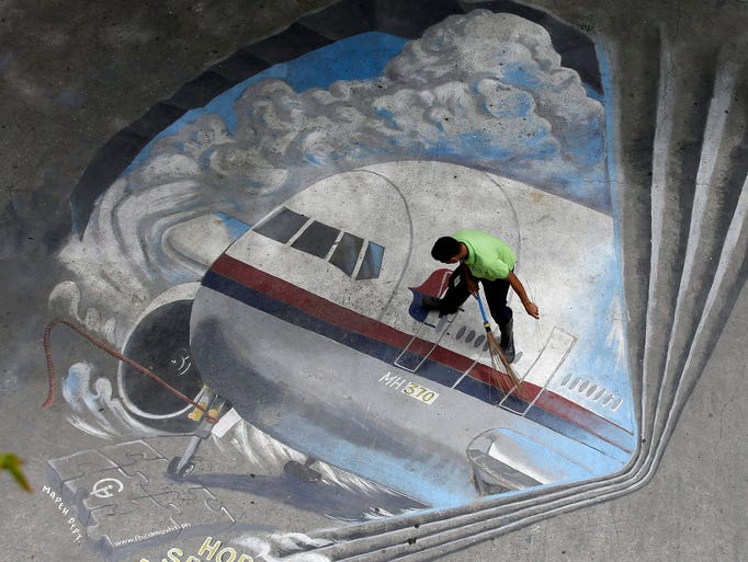 A worker cleans a painting of Malaysia Airlines Flight 370 at a school in Makati City on April 8 in Manila. The Boeing 777 with 239 people on board disappeared on March 8.