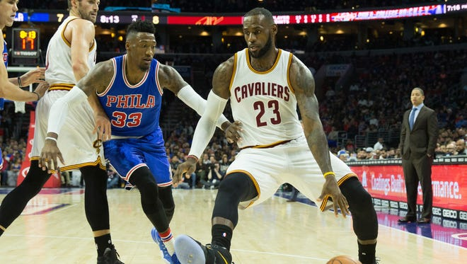 Cleveland Cavaliers forward LeBron James (23) dribbles past Philadelphia 76ers forward Robert Covington (33) during the first quarter at Wells Fargo Center.