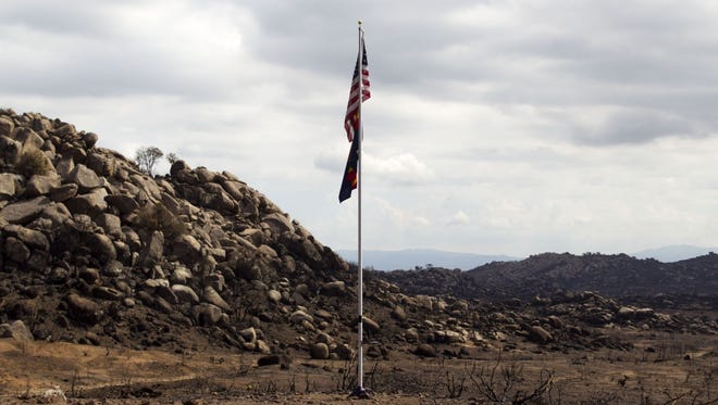An American flag and Arizona flag on a flagpole seen on Tuesday, July 23, 2013, near the site where 19 firefighters died fighting the Yarnell Hill Fire. The spot is expected to become a state park and memorial.