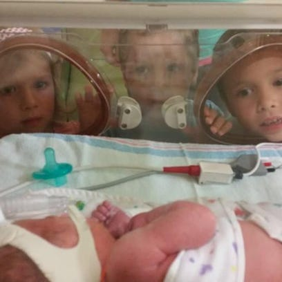 From left, Tinley, Gibson and Jamison Parsell look into the incubator of their baby sister, Macy, soon after her birth in August. Macy's twin sister, Sloan, died in August.