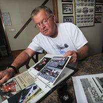 Longtime pit crew member and mechanic Ron Beavers looks through old photos from past Indianapolis 500 at his Sioux Falls home.