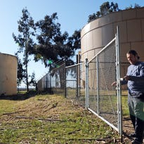 Horacio Amezquita, general manager of the San Jerardo Co-op enters the old well area. The tank on the right contains 325,000 gallons of clean water, which is pumped in from several miles away. The 30,000 gallon tank on the left is one of three closed down after toxins were found.