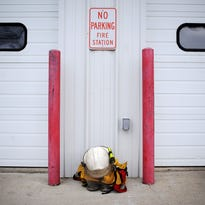 A firefighter's helmet and uniform sits outside the Valley Springs Fire Station on Wednesday in Valley Springs. Steve Ackerman, a Valley Springs Fire and Rescue volunteer firefighter, died on Sunday responding to a house fire that claimed the life of the homeowner, David Smith.