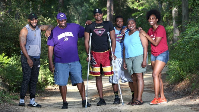 Cam Brown, who recently had his left leg amputated due to complications with osteosarcoma, an aggressive type of bone cancer, stands with his family at their home in Tallahassee. Family members are parents Sam and Michelle, their godson Rod Washington, brother Bin, and sister Maya.