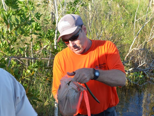 Microbiologist Dave Scott hands out plastic bags containing