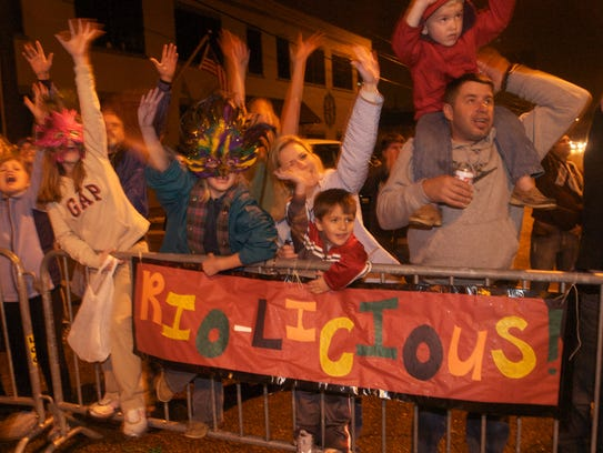 Parade  goers wave for beads during the Krewe of Rio