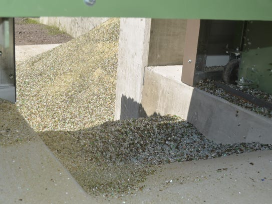 Crushed glass in fine and larger chunks fall from the