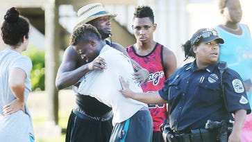 People comfort one another at the scene of a shooting at Club Blu in Fort Myers, Fla. where two people died and as many as 16 were injured in the early morning shooting July 25, 2016.