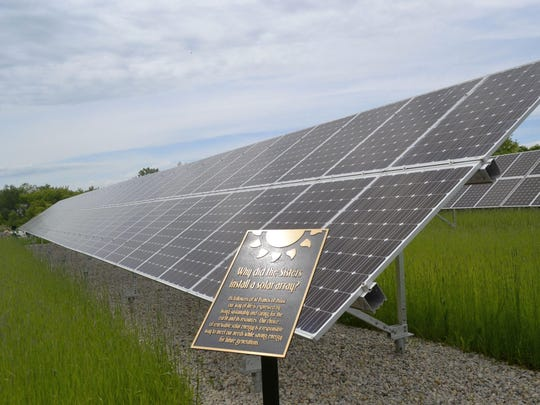 Sunlight is reflected at the top of one of the information plaques on the walking path for the solar-powered energy system on the convent grounds of Sisters of St. Francis of the Holy Cross in Green Bay during a dedication event June 18.