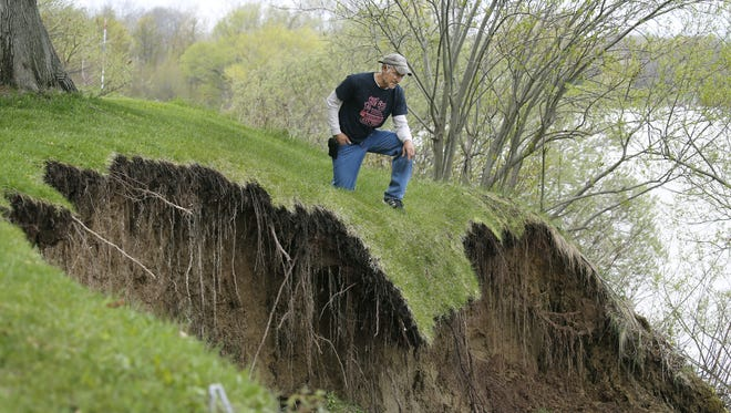 Rick Davis looks down at the portion of land he lost because of Lake Ontario's high level of water and the heavy rains at his property in Hamlin.