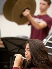 As Lillie Kang of YPAS  performs on flute,  percussionist Eric Meridian of Atherton claps his cymbals together.