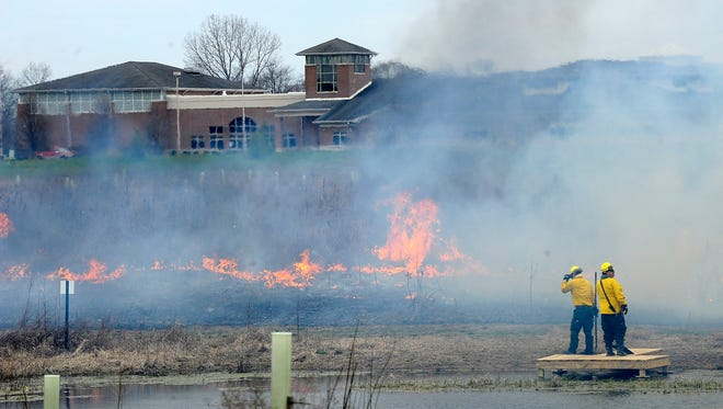 A team oversees a controlled burn at the Granville Exempted Village Schools' Land Lab on March 23, 2016.