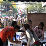 Anti-government protesters, in background, rally against advance voting as officials work at a polling station in Bangkok on Sunday.