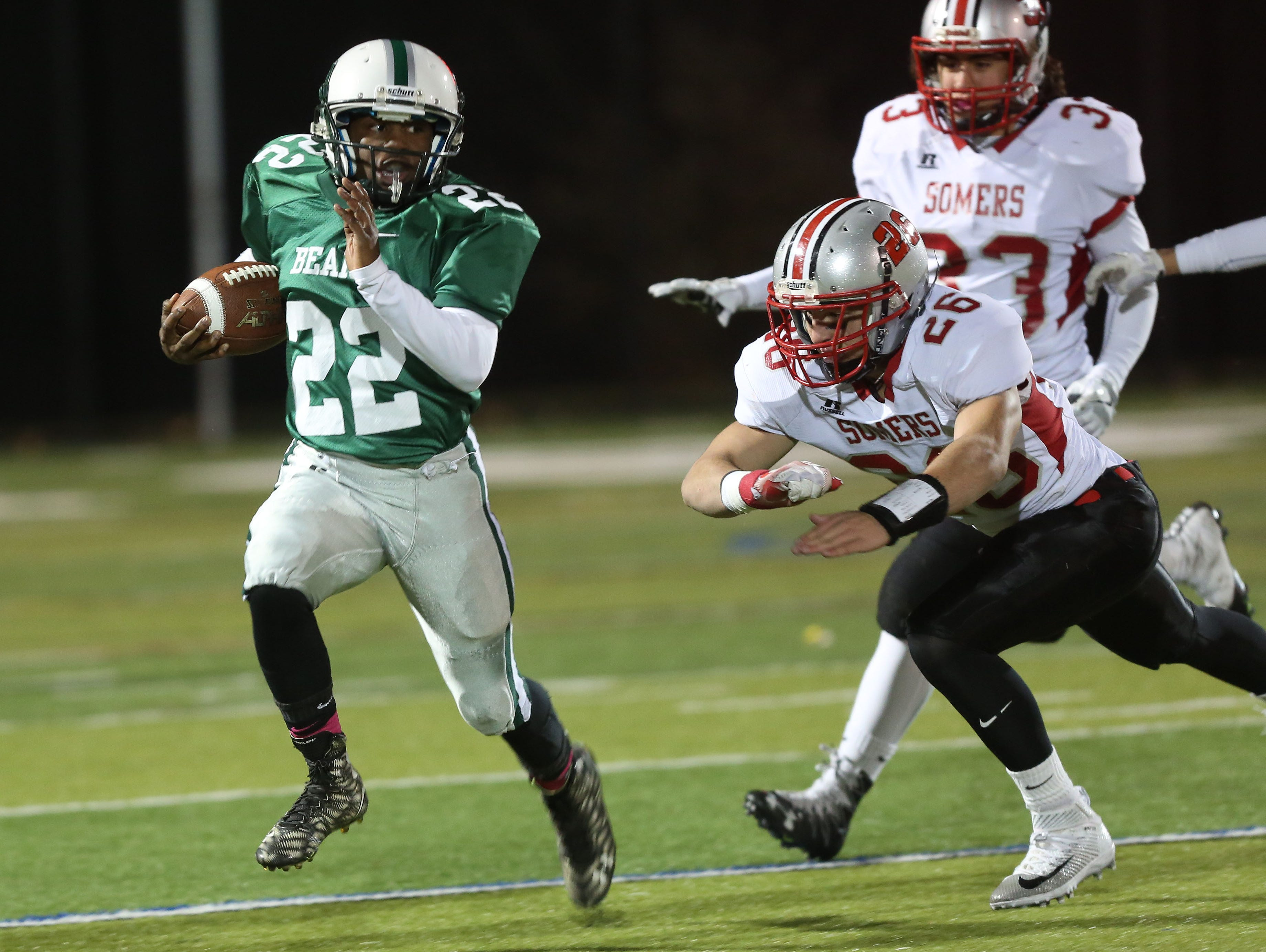 Brewster's Henry Terry (22) tries to get away from Somers Antonio Vieira (26) on first half run during the Section 1 Class A semifinals at Brewster High School Oct. 28, 2016.