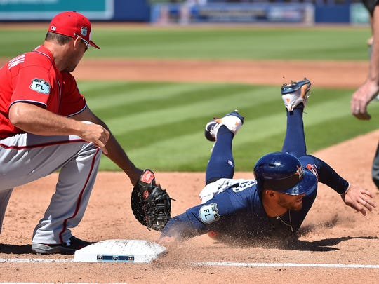 Houston Astros right fielder George Springer dives in safely ahead of the pick off attempt tag of Washington Nationals first baseman Ryan Zimmerman during a spring training game at The Ballpark of the Palm Beaches in West Palm Beach, Fla.