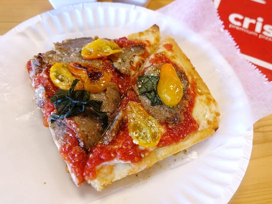 A traditional slice of pizza with meatballs and cherry