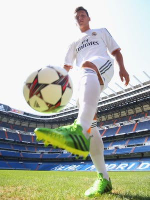 Mesut Oezil plays with the ball after the adidas presentation of the new campaign Welcoming Mesut to the family in the Adidas store in Madrid, Spain.
