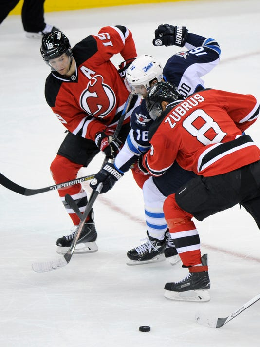 Winnipeg Jets' Andrew Ladd, center, is sandwiched by New Jersey Devils' Travis Zajac, left, and Dainius Zubrus, right, of Lithuania, during the second period of an NHL hockey game Thursday, Oct. 30, 2014, in Newark, N.J. (AP Photo/Bill Kostroun)