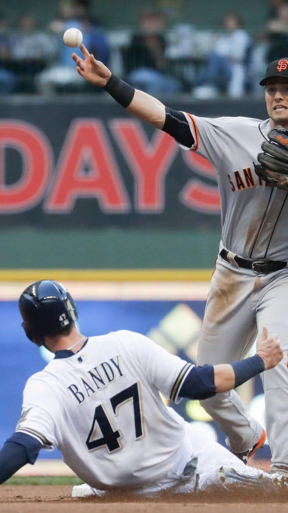 San Francisco Giants' Joe Panik makes a late throws as Milwaukee Brewers' Jett Bandy breaks up a double play on a ball hit by Keon Broxton during the second inning of a baseball game Tuesday, June 6, 2017, in Milwaukee. (AP Photo/Morry Gash)