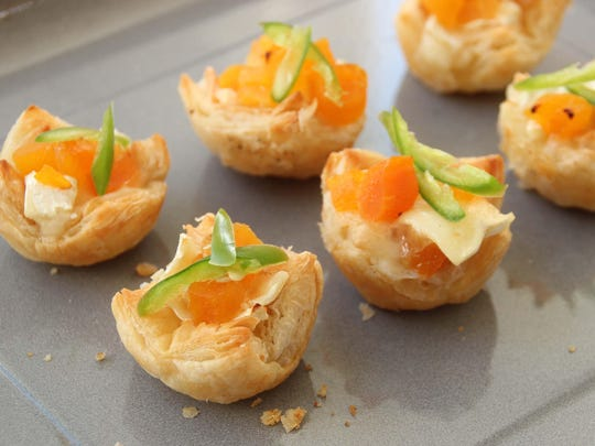 Puff pastry hors d'oeuvres are filled with brie, chopped apricots and topped with serrano chili.