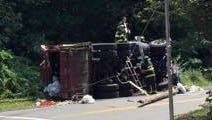 A garbage truck lies on its side after overturning Aug. 24, 2015, on South Pascack Road at Williams Road in Chestnut Ridge in this Journal News file photo. Four workers were injured.