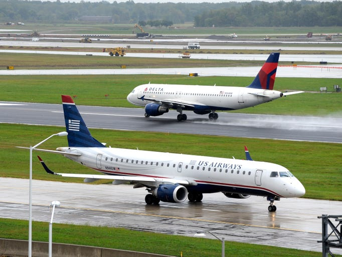 A Delta airliner takes off as a US Airways airliner,