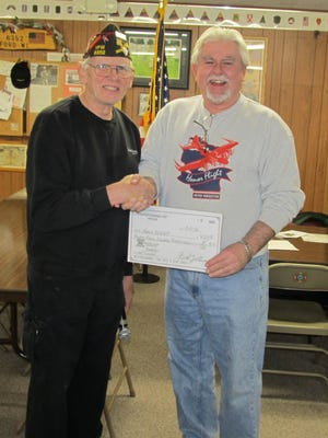 Commander Norbert Lee presents a check to Jim Campbell, co-chairman of the Never Forgotten Honor Flight, for $4,700. There were also matching funds of $500 from Marshfield Catholic Financial Life, which was sent to Jim Campbell.
