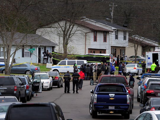Police investigate at a home on Vista Lane where three people were found dead Monday morning.