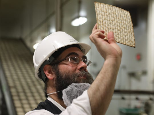 Rabbi Aron Hayum, plant manager at Manischewitz in Newark, looking over a matzo that just came out of the oven. Rabbis on the production line check to make sure matzos have been made following kosher guidelines.