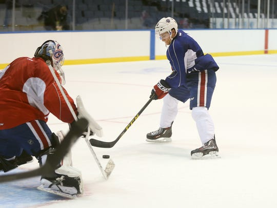 The Amerks Matt Garbowsky attacks with the puck against goalie C.J. Motte during a training camp earlier this week.