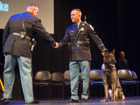"Vineland K-9 Officer Derrick Magee, right, and his K-9 partner Fifa are congratulated by Vineland K-9 Officer Dwight Adams as K-9 Officer Magee and his K-9 partner Fifa walk the stage to receive their graduation plaque during the Atlantic County Police Training Center John ""Sonny"" Burke K-9 Training Center Graduation Ceremony held at the Atlantic County Institute of Technology in Mays Landing on Friday, June 29, 2018."
