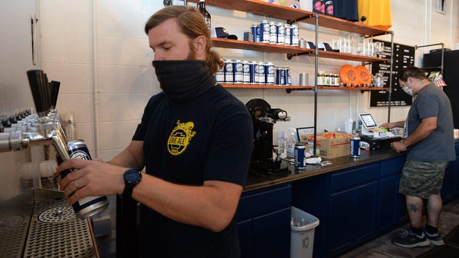 Jeff McCullor, left, co-owner of Erie Ale Works and bartender Mario Castelluccio, right, serve customers. The Erie business completed a recent expansion just as the COVID-19 pandemic hit.