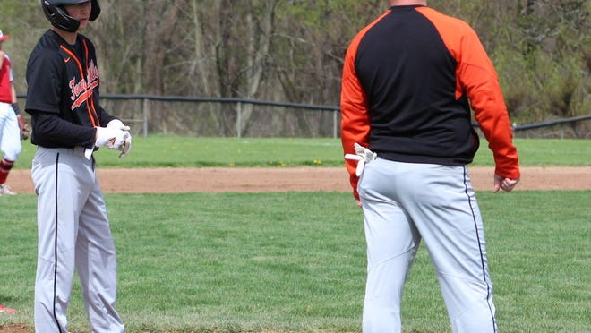 Brody Peterson (left) talks with his dad and coach, Steve Peterson (right) during a baseball game.