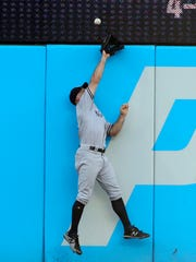 New York Yankees' Brett Gardner jumps at the wall but can't catch an RBI double by Cleveland Indians' Yan Gomes during the second inning of a baseball game Friday, July 13, 2018, in Cleveland.