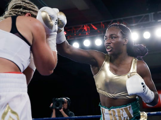 Claressa Shields, right, hit Nikki Adler, of Germany, during the second round of the women's WBC super middleweight boxing bout, Friday, Aug. 4, 2017, in Detroit. (AP Photo/Carlos Osorio)