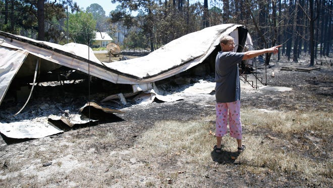 Amanda Hall, a resident of  stands in front of the remains of her destroyed trailer as she recalls the moments she and her friend Rick Shepard saw the fire coming towards their home on Wilderness Drive in Easpoint.