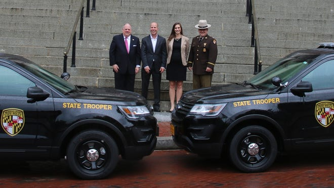 Gov. Larry Hogan, Hardwire Founder and CEO George Tunis, Hardwire President and COO Emily Tunis and Colonel William Pallozzi of the Maryland State Police stand in front of the two newly armored Ford Explorers