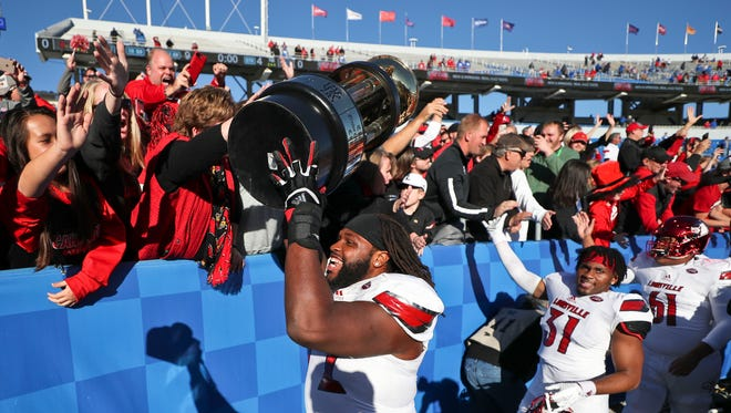 Louisville's Lukayus McNeil holds up the Governor's Cup after Louisville easily beat Kentucky 44-17 Saturday Nov. 25.