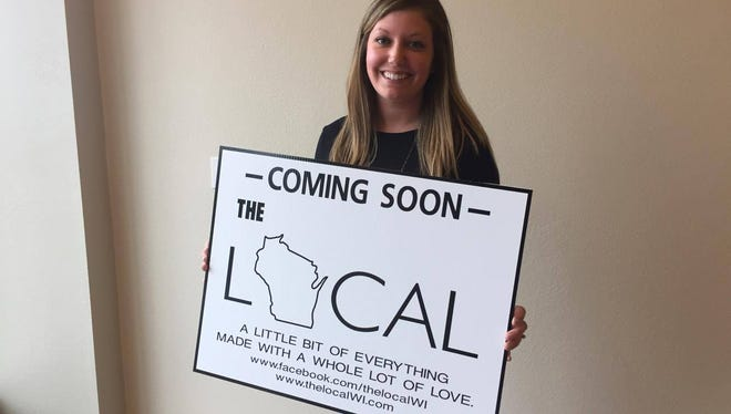 Alison Magnuson, 26, holds a sign for The Local, the newest store coming to downtown Wausau this summer.