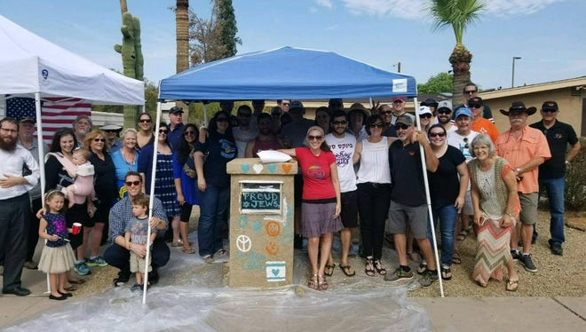 About 100 family, friends and neighbors help Shoshana and Ari Simones cover up anti-Semitic graffiti on their mailbox Sunday, July 9, 2017, in Phoenix.