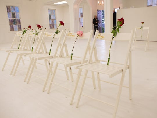 Chairs adorned with roses Sunday, Nov. 12, 2017, mark