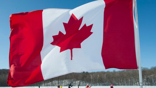 Competitors ski past a Canadian flag during the freestyle cross-country ski event at the Gatineau Loppet, in 2015 in Gatineau, Quebec.