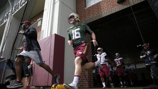 FSU's J.J. Cosentino runs out to the field during the first day of spring practice at the Dunlap Training Facility on the school's campus on Wednesday. He took first-team snaps at quarterback.