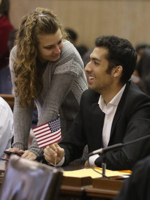 Aria Fazeli of Rochester was one of 44 people who became naturalized citizens during a ceremony at the Monroe County building.  Fazeli, of Iran, and his girlfriend, Hannah McCullough, are undergraduate students at the University of Rochester.  Fazeli along with other soon-to-be citizens, filled out his voter registration cards.