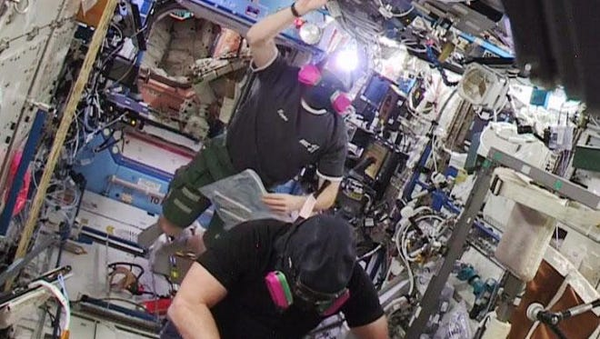 Expedition 42 crew members re-enter the American segment of the International Space Station with masks at 3:05 p.m. ET Wednesday, Jan. 14, 2015.